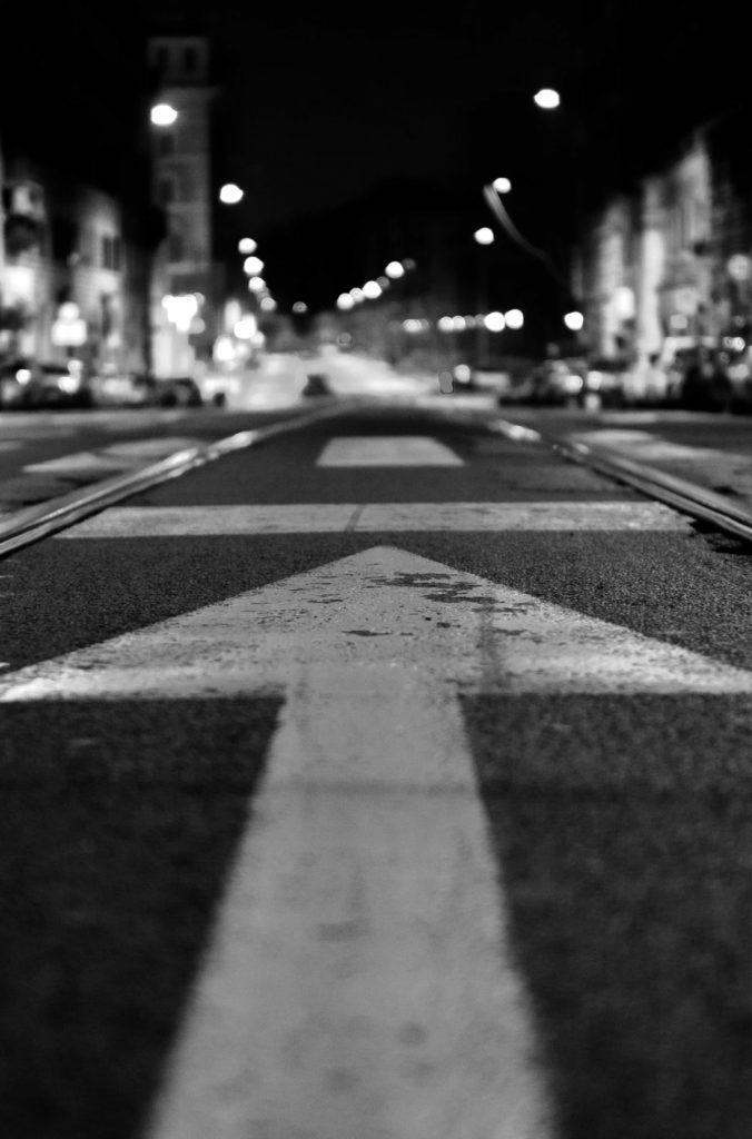 City street with arrow painted on ground and photo taken with a ground shot